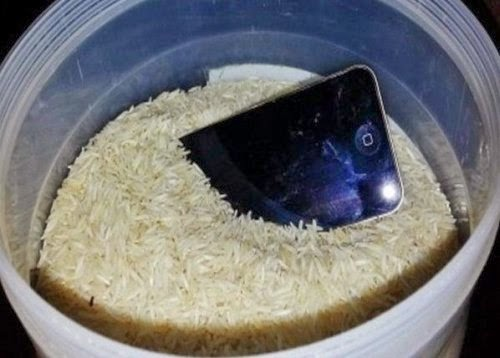 Phone and battery with uncooked rice in the container